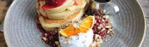 Ingredienti per colazione proteica facile: pancake, frutta, formaggio fresco