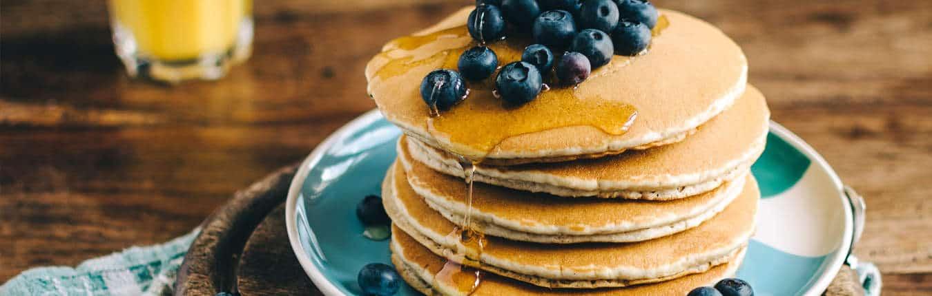 Uova a colazione sotto forma di pancake con sciroppo e mirtilli