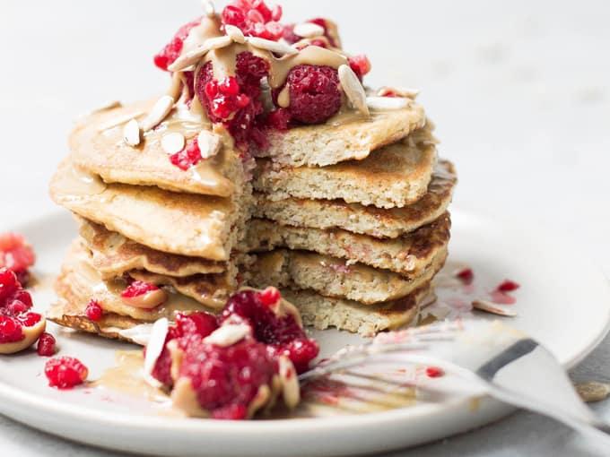 Pancakes di farina d'avena con crema, frutti rossi e semi su piatto bianco