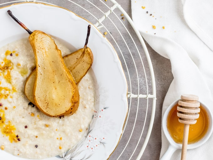 Porridge con miele, semini e pera cotta su piatto bianco