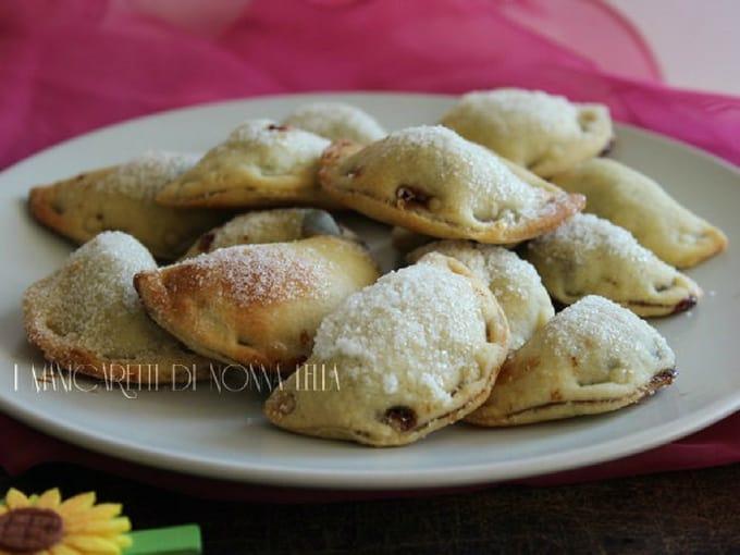 Pastatelle, dolci a mezzaluna ricoperti di zucchero in un piatto